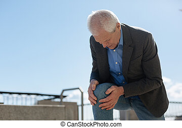 Retired man cutting up about his knee outdoors