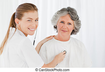 Retired patient with her nurse looking at the camera