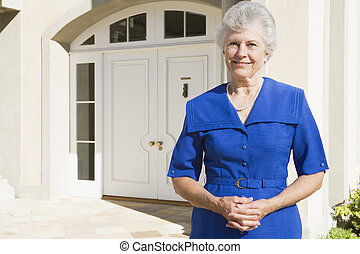 Retired woman standing outside house