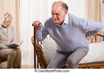 Retired man using walking stick having backache
