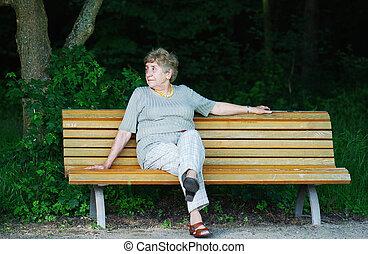retiree sitting alone on park bench