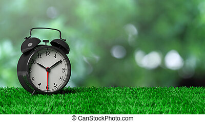 Retro alarm clock on grass with abstract green bokeh background