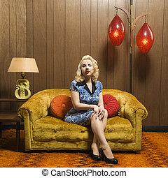 Attractive Caucasian woman sitting in retro decorated room.