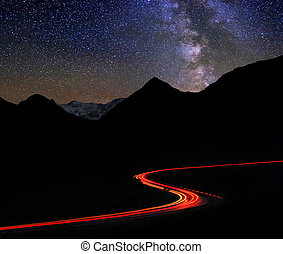 Road in the mountains under a starry gyres