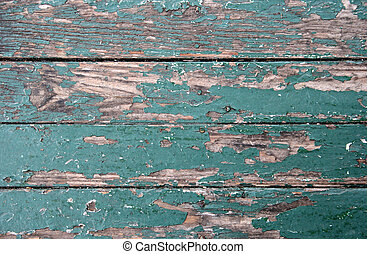 Old worn floorboards with sun-faded peeling green paint.