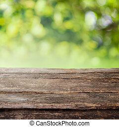 Rustic weathered cracked wooden country fence plank or table top against a blurred background of greenery and foliage in summer sun
