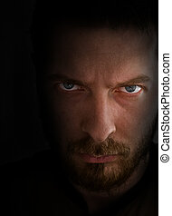 Low-key portrait - sad and angry looking man