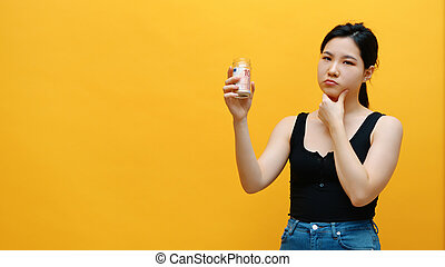 Sad pensive young asian woman holding money jar with savings. Low income and big expenditure concept