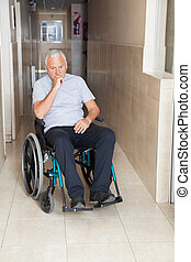 Sad Senior Man Sitting In a Wheelchair