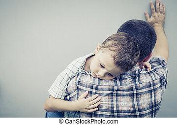 sad son hugging his dad