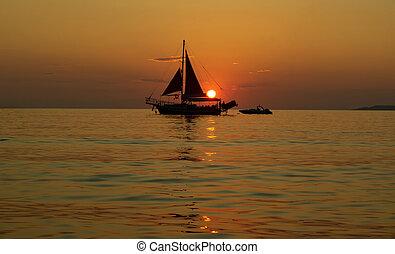 Sailing ship at sea at sunset