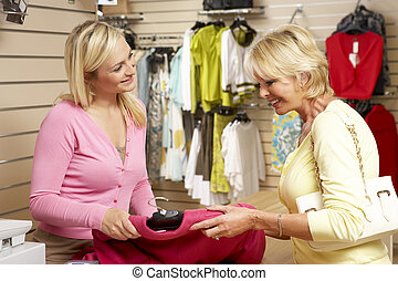 Sales assistant with customer in clothing store