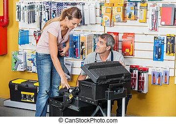 Salesman Guiding Customer In Selecting Tools At Store