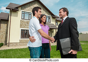 Salesman shaking hands with property owners. Handshake deal with young couple outside on lawn