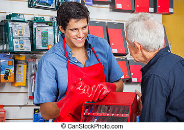 Salesman Showing Drill Bit To Man In Store