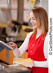Saleswoman Preparing Cheese Bill At Grocery Counter