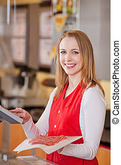 Saleswoman Preparing Meat Bill At Grocery Counter