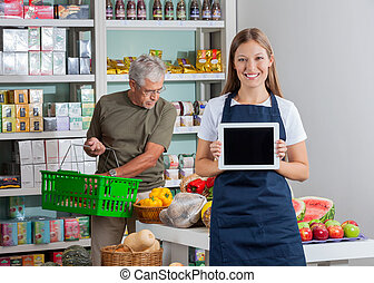 Portrait of saleswoman showing digital tablet while senior man shopping in background