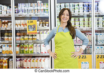 Portrait of confident mature saleswoman standing with hands on hip against products displayed in refrigerator