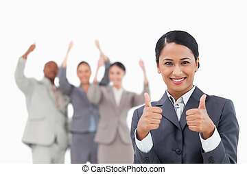 Saleswoman with cheering team behind her giving approval against a white background