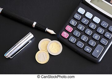 save money concept with calculator and euro money coins on black