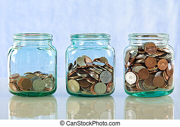Saving money concept - coins in old jars on reflective surface against blue background