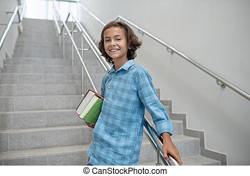 Happy schoolboy standing on stairs, holding pile of books