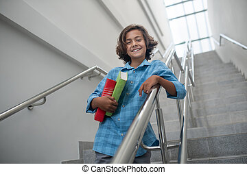 Schoolboy leaning on stair railing, holding pile of books