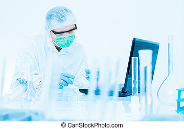 scientist working in the lab, in protective mask and cap, examines a test tube with liquid