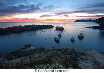 Beautiful view of the sea at twilight in Riomaggiore, Italy - blurred boat due to long exposure