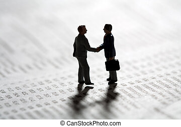 Two tiny miniature figurines of businessman standing in silhouette on a statistical document sealing a business transaction with a handshake