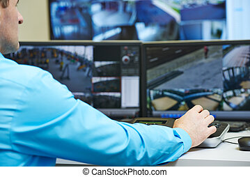 security guard watching and operating video monitoring surveillance security system