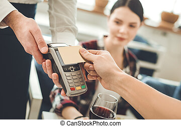 Selective focus of a credit card in the hands of a a waiter