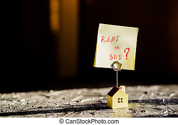 Selective focus of house model, poster , yellow sticker with notes written with 'BUY OR RENT?'. Real estate theme. Text message Buy or rent . Business concept