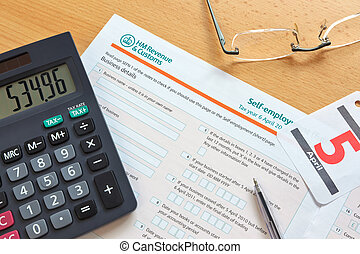 Photo of a UK self employment tax form, the deadline for the tax year is 5th April as shown by the calendar.