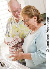Senior Adult Couple Washing Dishes Together Inside Kitchen