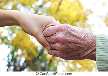 Young and senior holding hands in autumn