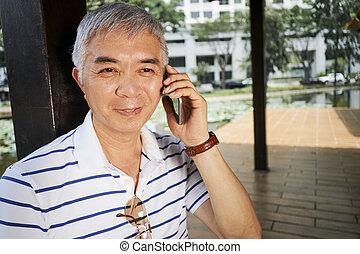 Senior Chinese man talking on phone