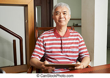 Senior Chinese man with tablet computer