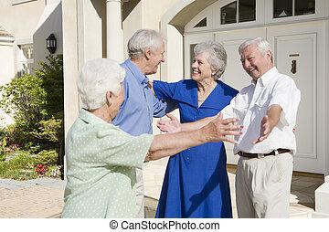 Senior couple greeting friends
