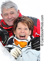 Senior couple having a great time skiing