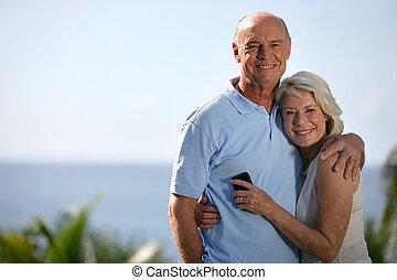 Senior couple hugging outdoors
