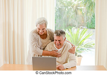 Senior couple looking at their laptop