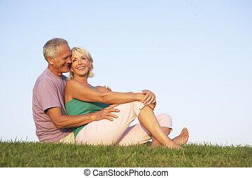 Senior couple posing on a field