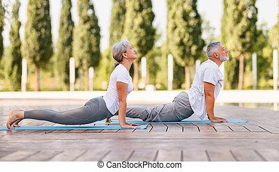 Senior couple practicing Bhujangasana while doing yoga together in park on sunny morning