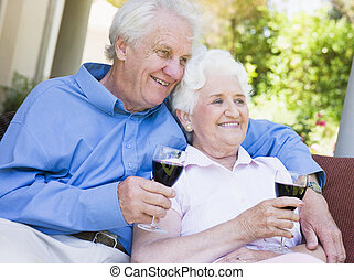 Senior couple sitting outdoors having a glass of red wine