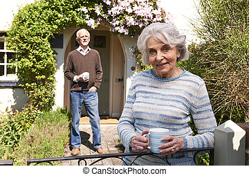 Senior Couple Standing In Cottage Garden With Coffee Cups