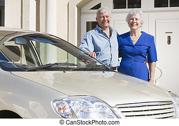 Senior couple standing with their car outside their home