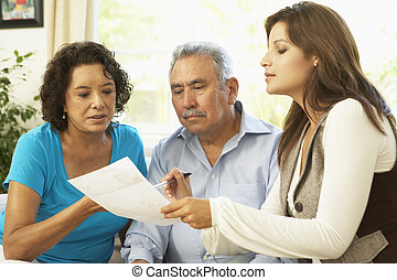 Senior Couple With Financial Advisor At Home