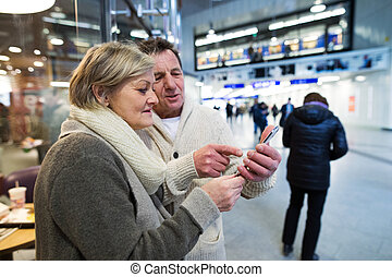 Senior couple with smartphone in hallway of subway